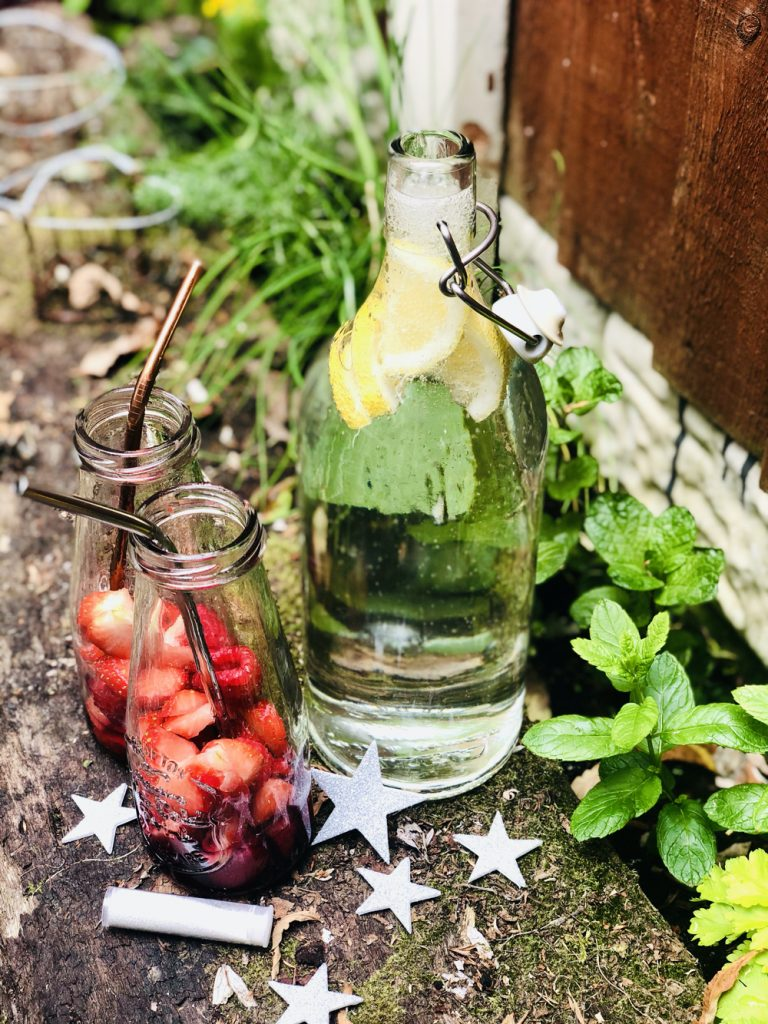 bottle of lemonade thats just been opened fizzing, two small glass bottles stuffed with strawberries and raspberries stood on an old wooden sleeper by the bottle