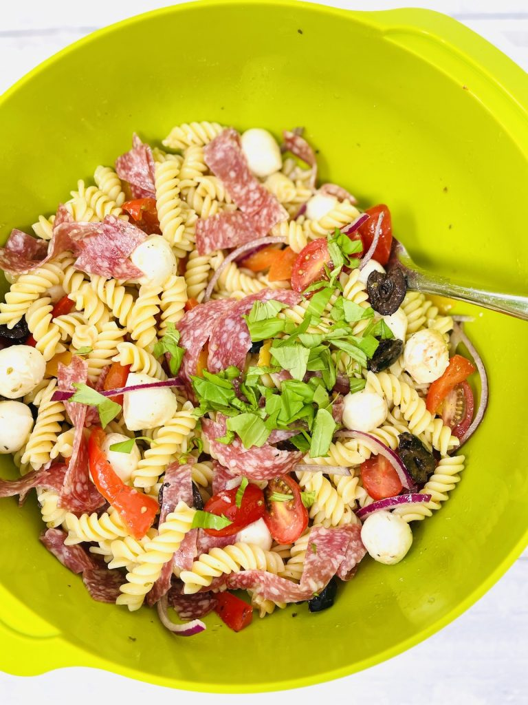 italian pasta salad sprinkled with chopped basil leaves