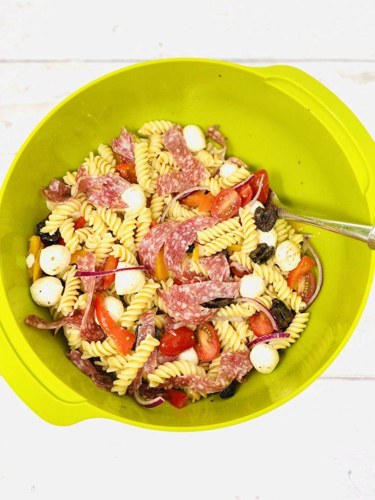 easy Italian pasta salad being tossed in Italian dressing