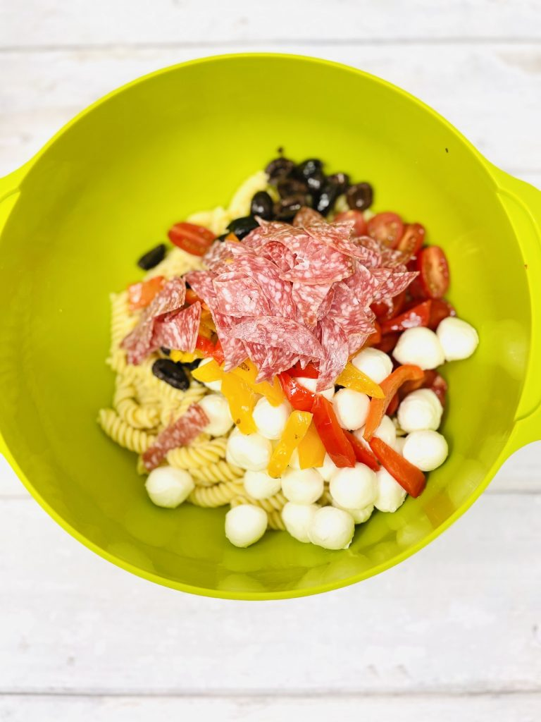 easy italian pasta salad ingredients in a mixing bowl - fusilli pasta, mozzarella balls, black olives, chargrilled peppers, juicy tomatoes
