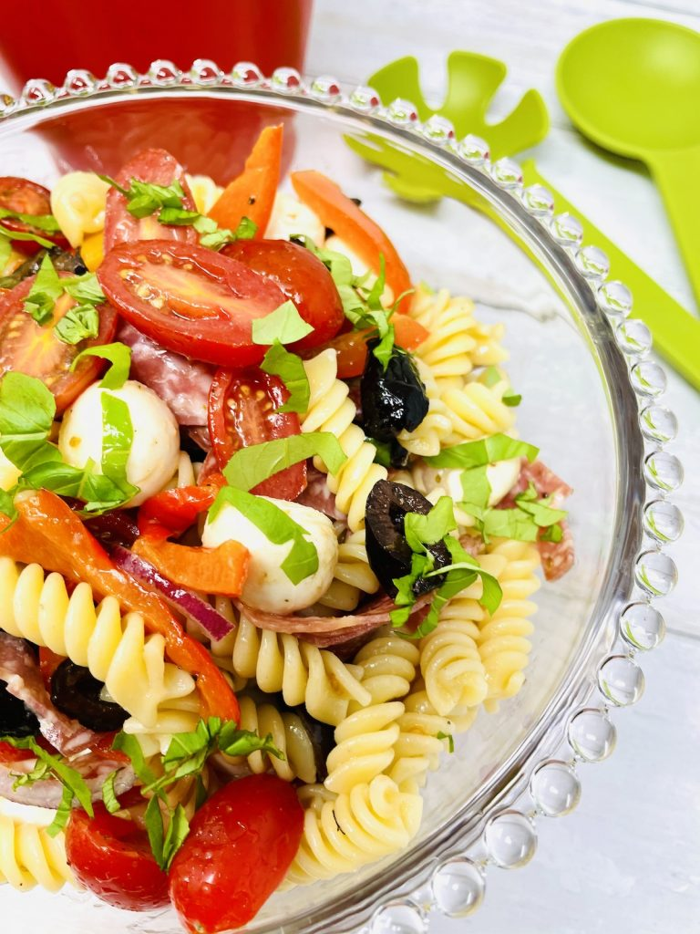 easy italian pasta salad with red onions, mozzarella, black olives, baby plum tomatoes, chargrilled peppers and salami