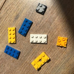 blue, yellow, grey and white LEGO pieces on a wooden laminate floor