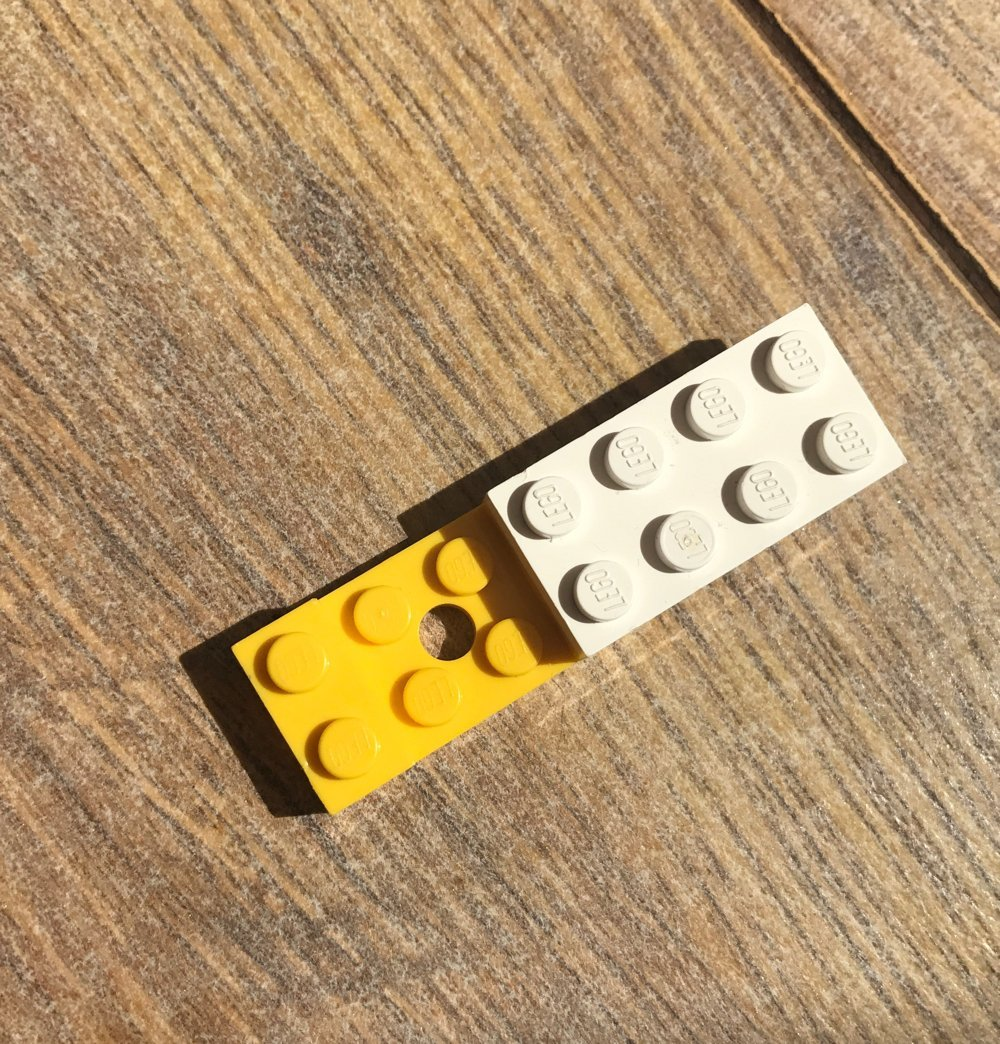 yellow and white LEGO pieces fitted together on wooden laminate floor