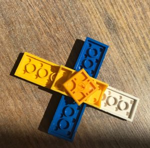 LEGO pieces fitted together to make a fidget spinner - on a wooden laminate floor