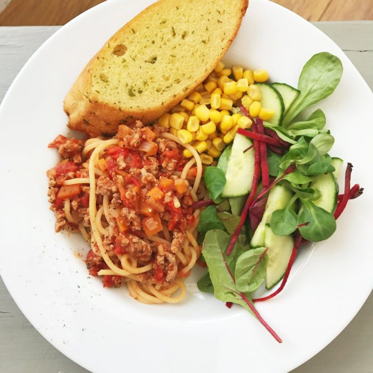 white plate with turkey bolognese, garlic bread, mixed green salad and sweetcorn
