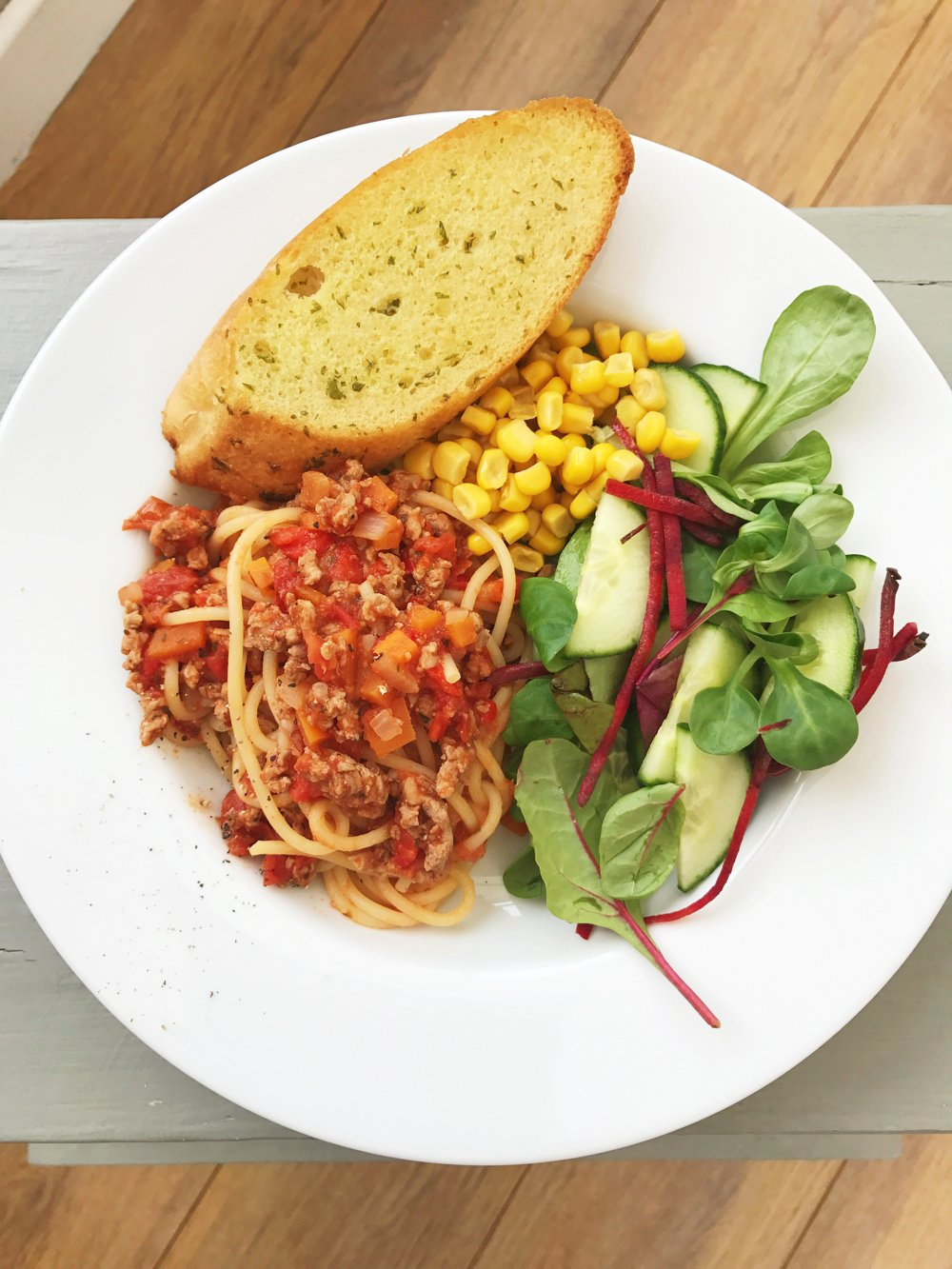 plateful of homemade turkey bolognese served with garlic bread, salad and sweetcorn
