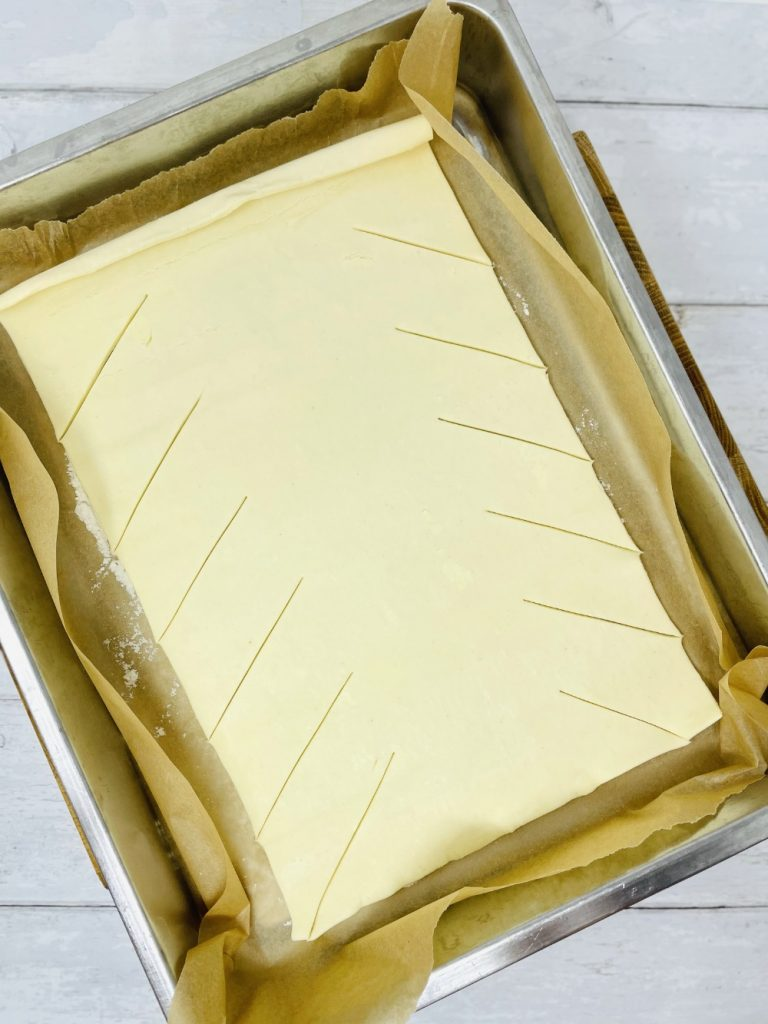 puff pastry sheet with slants cut into the side ready to make a cheese and ham pie