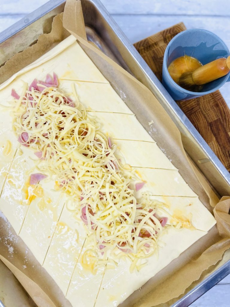 puff pastry sheet with slits cut into the sides of the pastry - middle filled with ham and grated smoked cheese