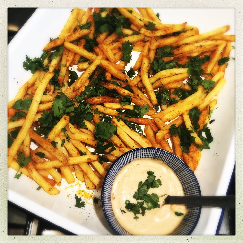 white enamel roasting tin with homemade spicy oven fries and a small blue and white dish filled with harissa mayonnaise.