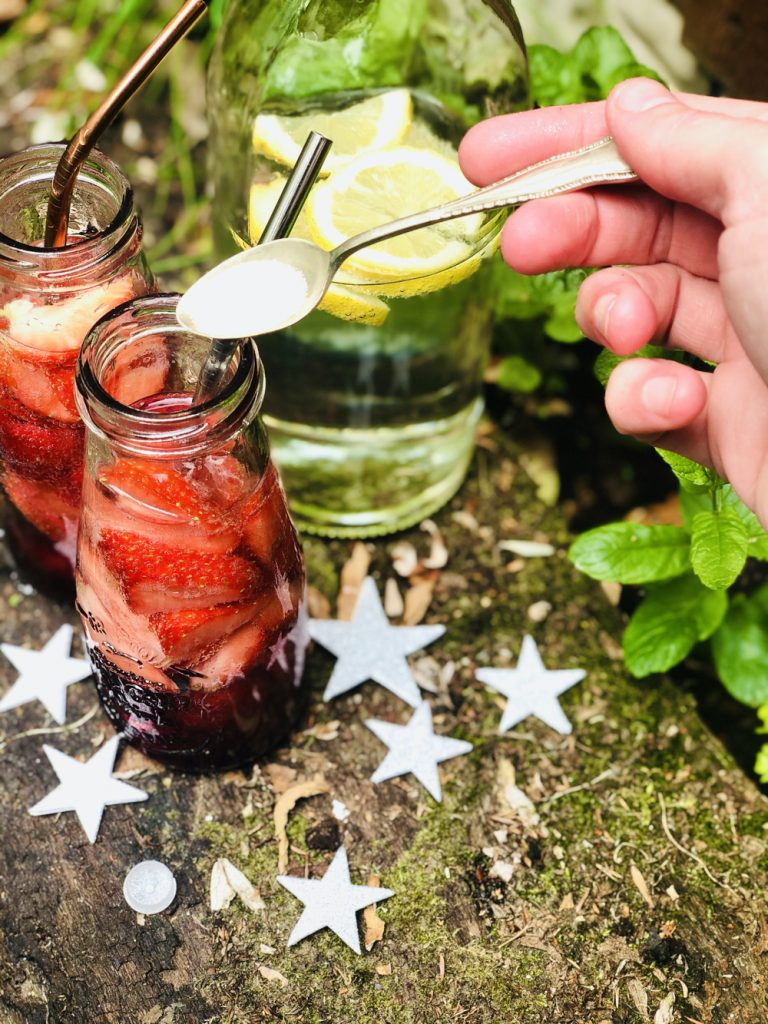 a vintage teaspoon with edible glitter on it waiting to be tipped into a homemade fairy portion summer fruit drink in glass bottles with strawberries and raspberries