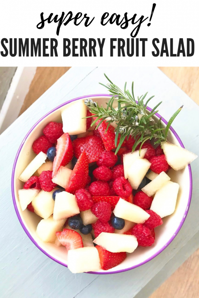 "summer berry fruit salad with strawberries, raspberries, blueberries and melon served in an enamel bowl with sprig of rosemary. Text overlay reads ""super easy summer berry fruit salad"""