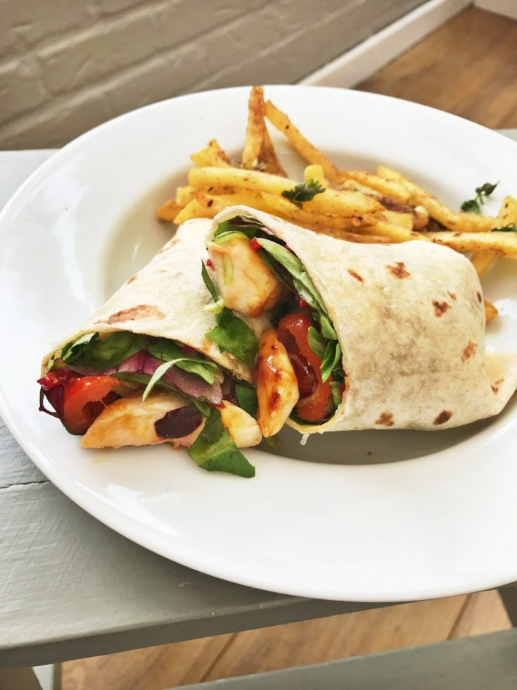 sweet chilli chicken wrap with salad and a side of spicy salt and pepper chips
