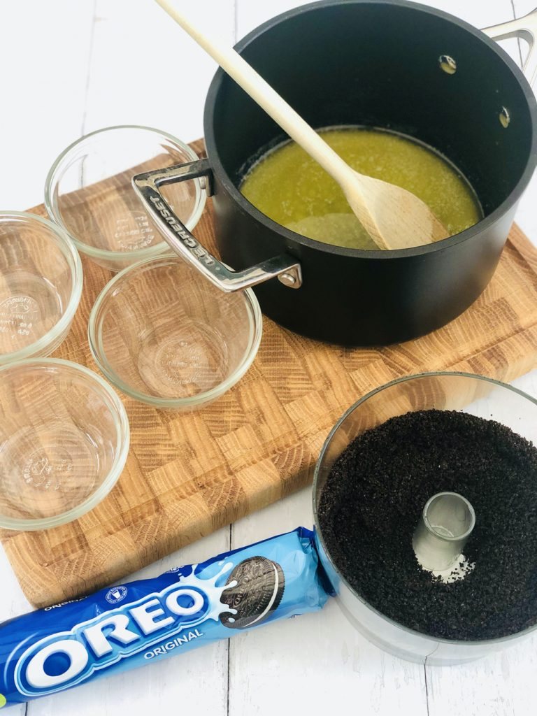melted butter in a saucepan alongside oreo crumbs and four mini custard dishes ready to be filled with oreo cheesecake biscuit base