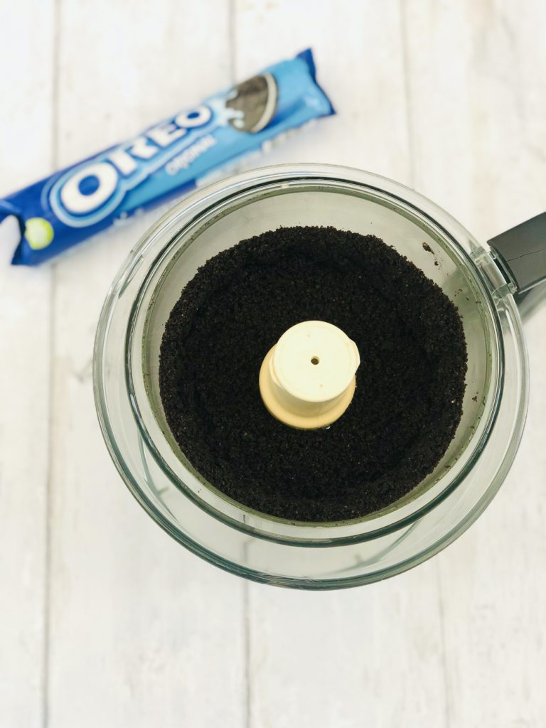 oreo biscuits that has been blitzed into biscuit crumbs in a magimix food processor - packet of oreos alongside the mixer bowl