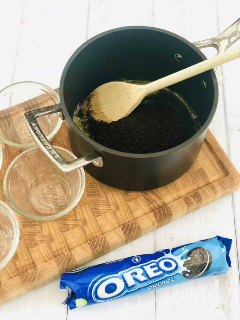 oreo biscuit crumbs being tipped into a saucepan with melted butter