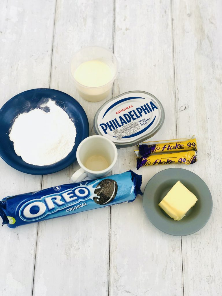 Ingredients for mini oreo cheesecakes - packet of oreos, block of butter, 2 mini flakes, pot of philadelphia cream cheese, tsp vanilla extract, double cream and icing sugar