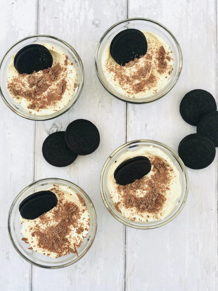 mini oreo cheesecakes with oreo biscuits in stood in the creamy cheesecake topping