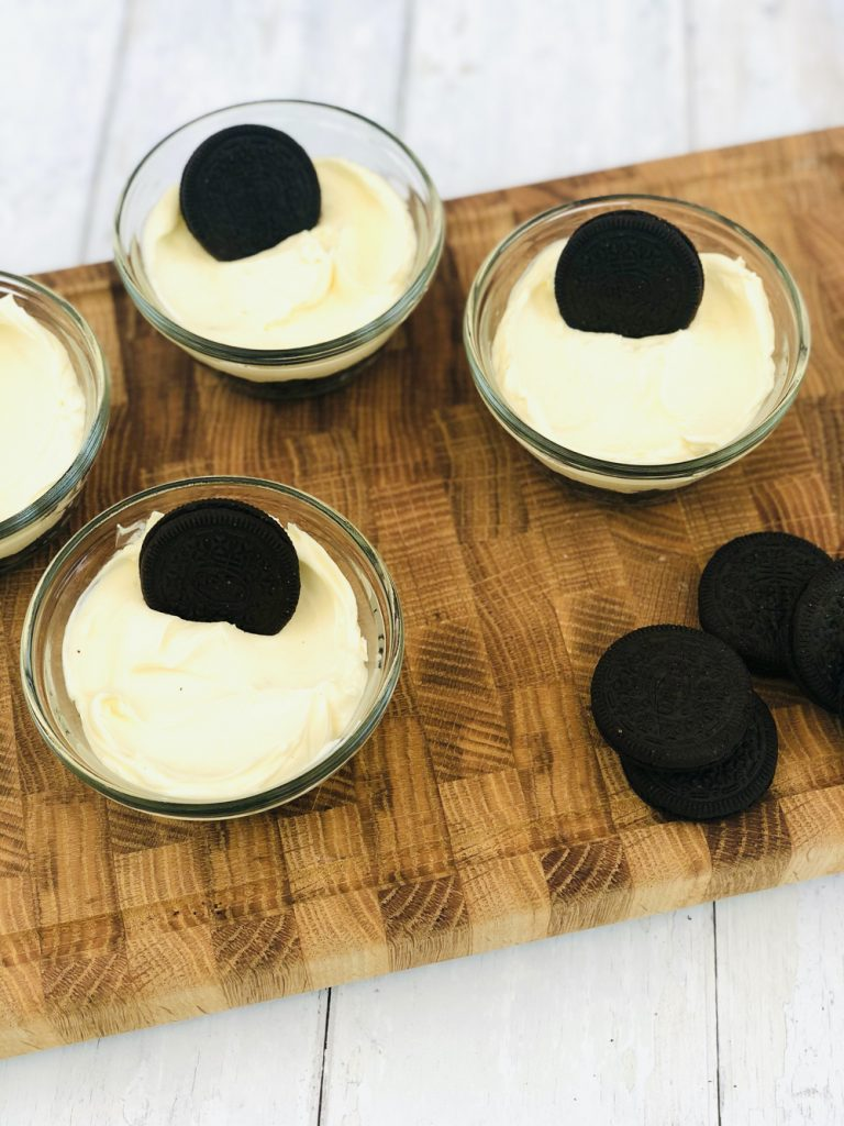 oreo biscuits being stood up in the oreo cheesecake topping as a decoration