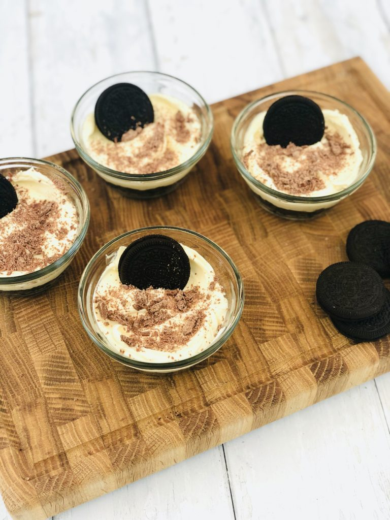 mini oreo cheesecakes sprinkled with chocolate flake with an oreo stood up in the creamy cheesecake topping