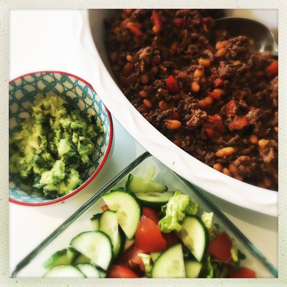 bowl of 20 minute beef and baked bean chilli alongside homemade guacamole and green salad