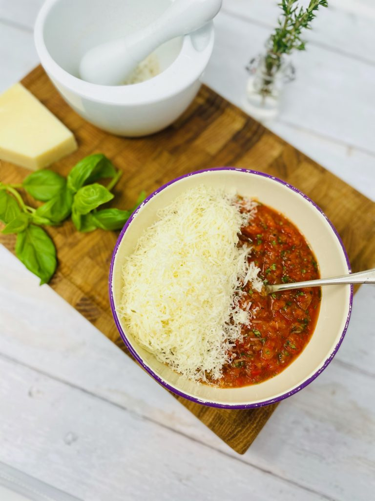 grated Parmesan being added to red pesto