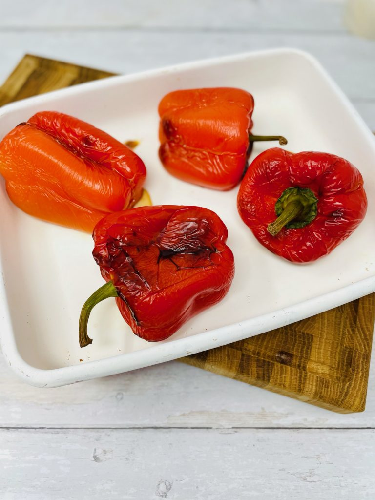four roasted red peppers in an enamel baking tray