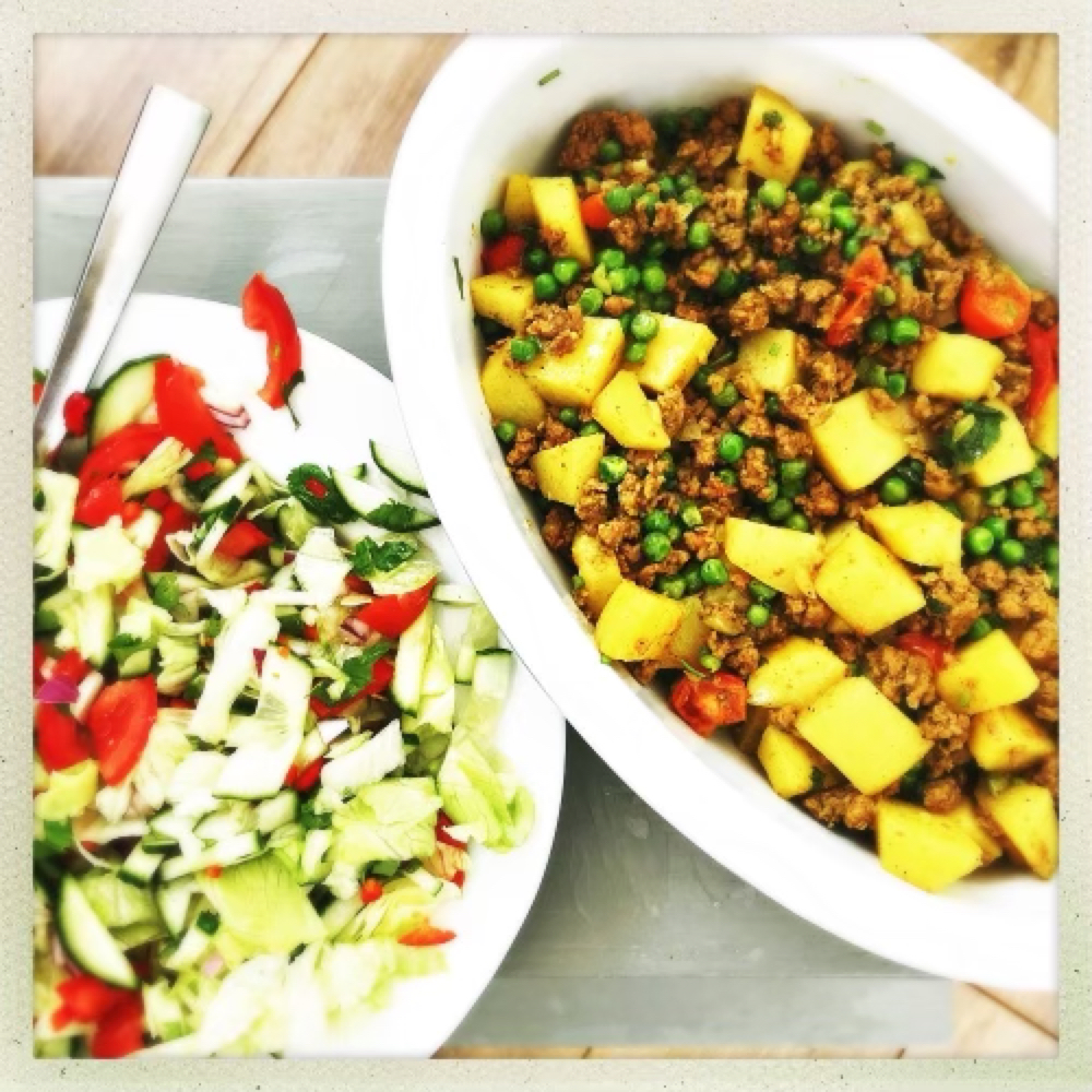 lamb and potato curry in a serving bowl alongside Indian salad