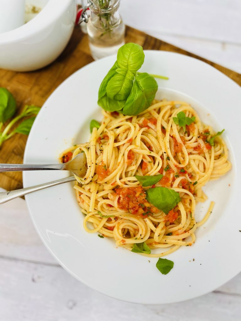 red pesto stirred through spaghetti scattered with basil