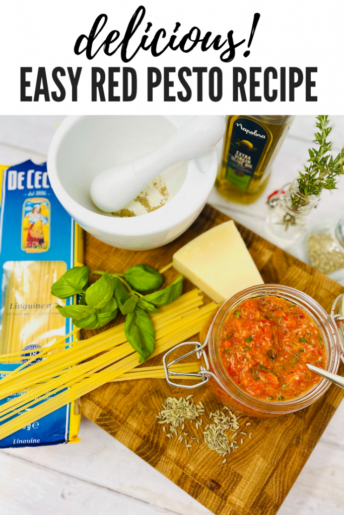 """red pesto on a board with red pesto ingredients - parmesan, basil leaves, fennel seeds and olive oil. Pack of linguine is spilled open. Text overlay """"delicious easy red pesto recipe"""""""