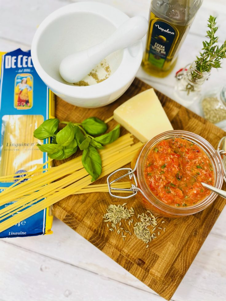 red pesto on a board with red pesto ingredients - parmesan, basil leaves, fennel seeds and olive oil. Pack of linguine is spilled open
