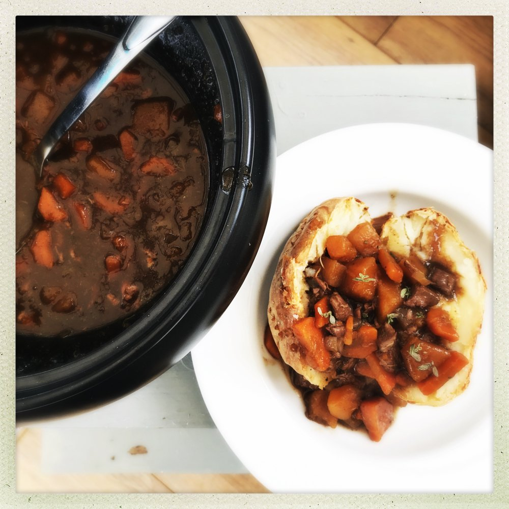 slow cooker lamb stew served in an oven baked potato