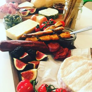 autumn cheese board with cheese, figs, fruit, nuts, ham and french saucisson
