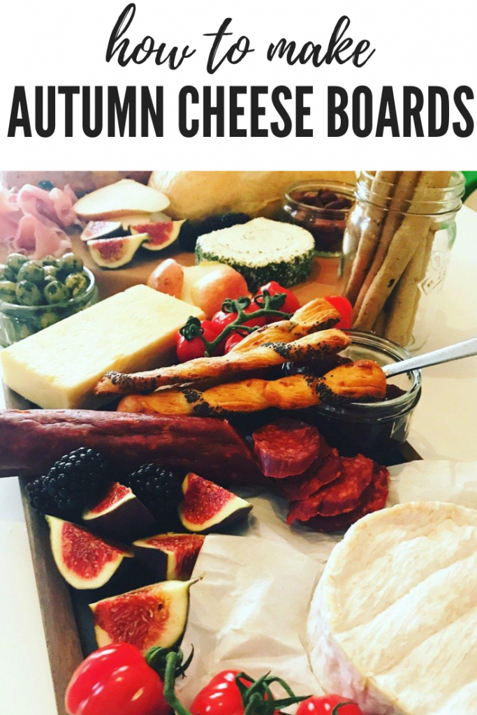 how to make a cheese board for autumn - large grazing board with cheese, charcuterie, olives, parma ham, figs, smoked nuts, bread sticks and seasonal fruit and vegetables