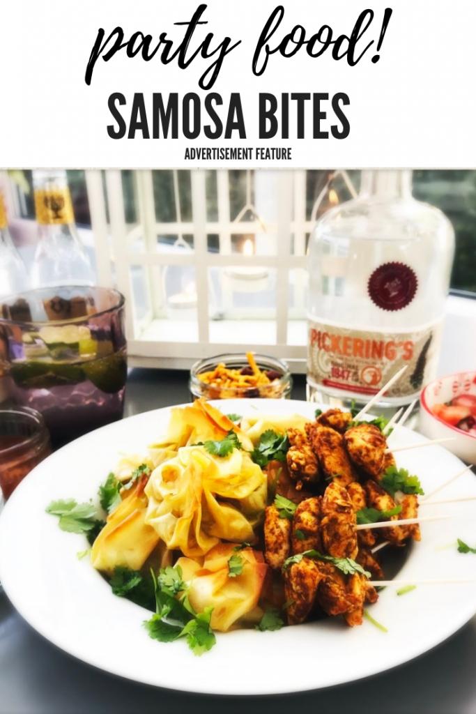 """vegetable samosa bites on an Indian party food platter with spicy chicken skewers and bottle of pickings gin in background. Text overlay reads """"party food samosa bites"""""""