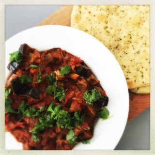 aubergine stew - a vegan stew made with aubergines and tomato, served in a white bowl scattered with chopped flat leaf parsley and served with a garlicky naan bread