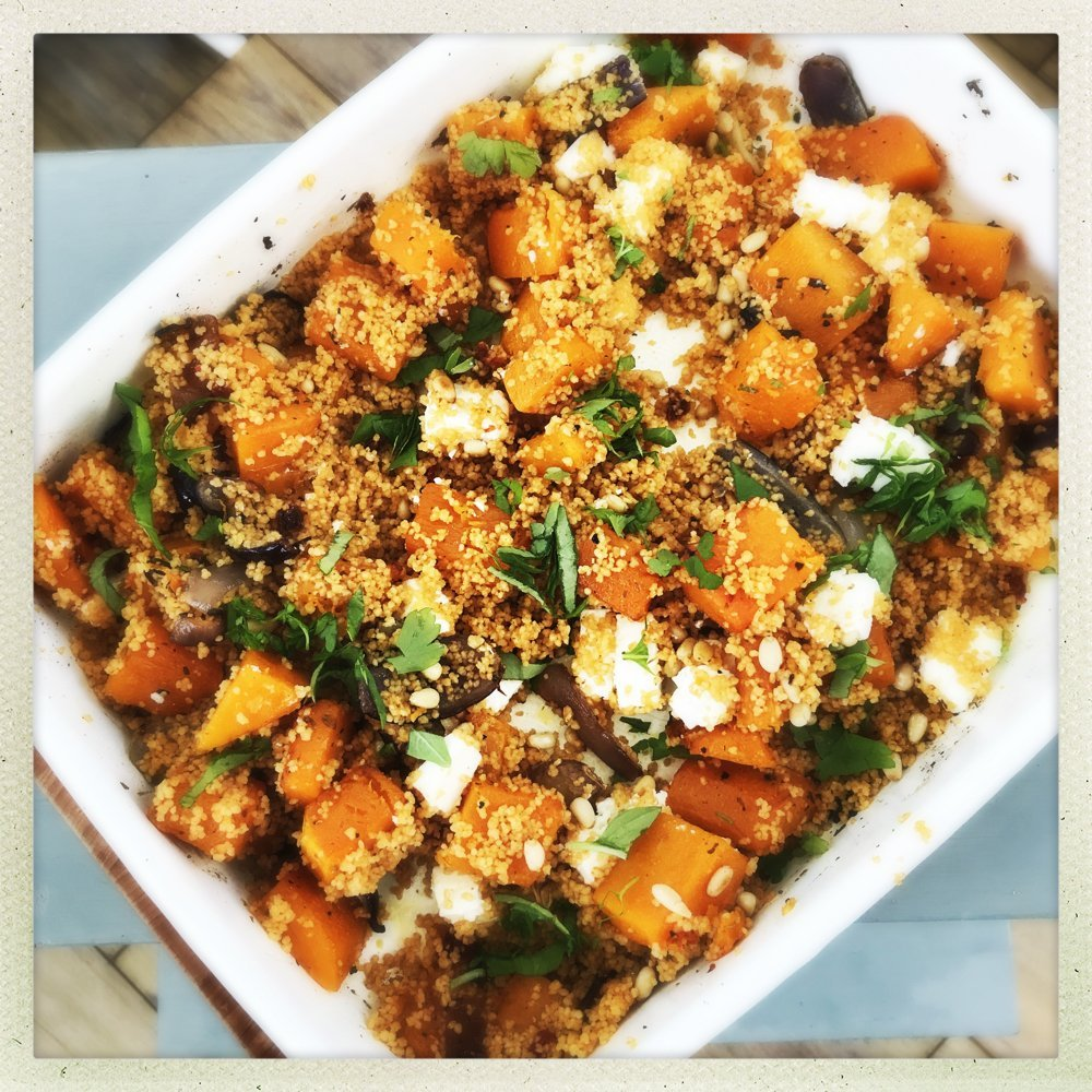 enamel roasting tin filled with roast butternut squash and feta couscous scattered with chopped flat leaf parsley