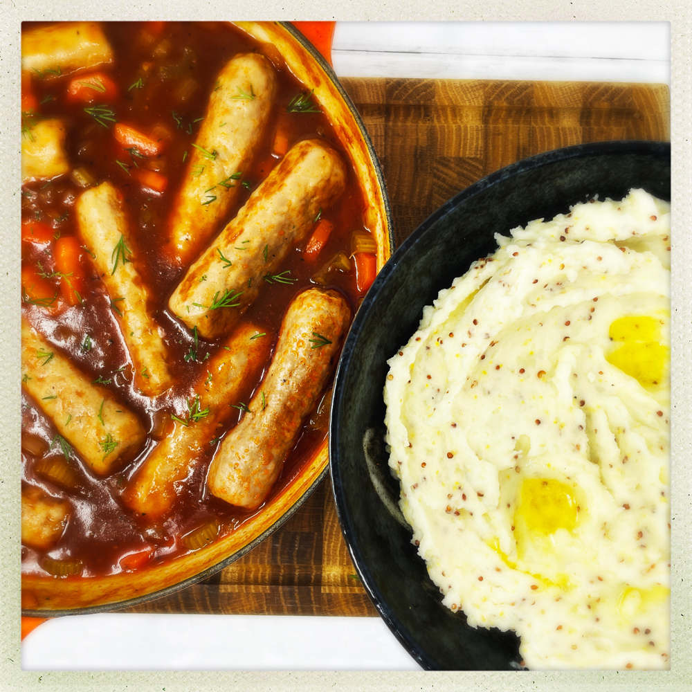 easy sausage casserole served in a skillet pan next to a bowlful of mustard mash