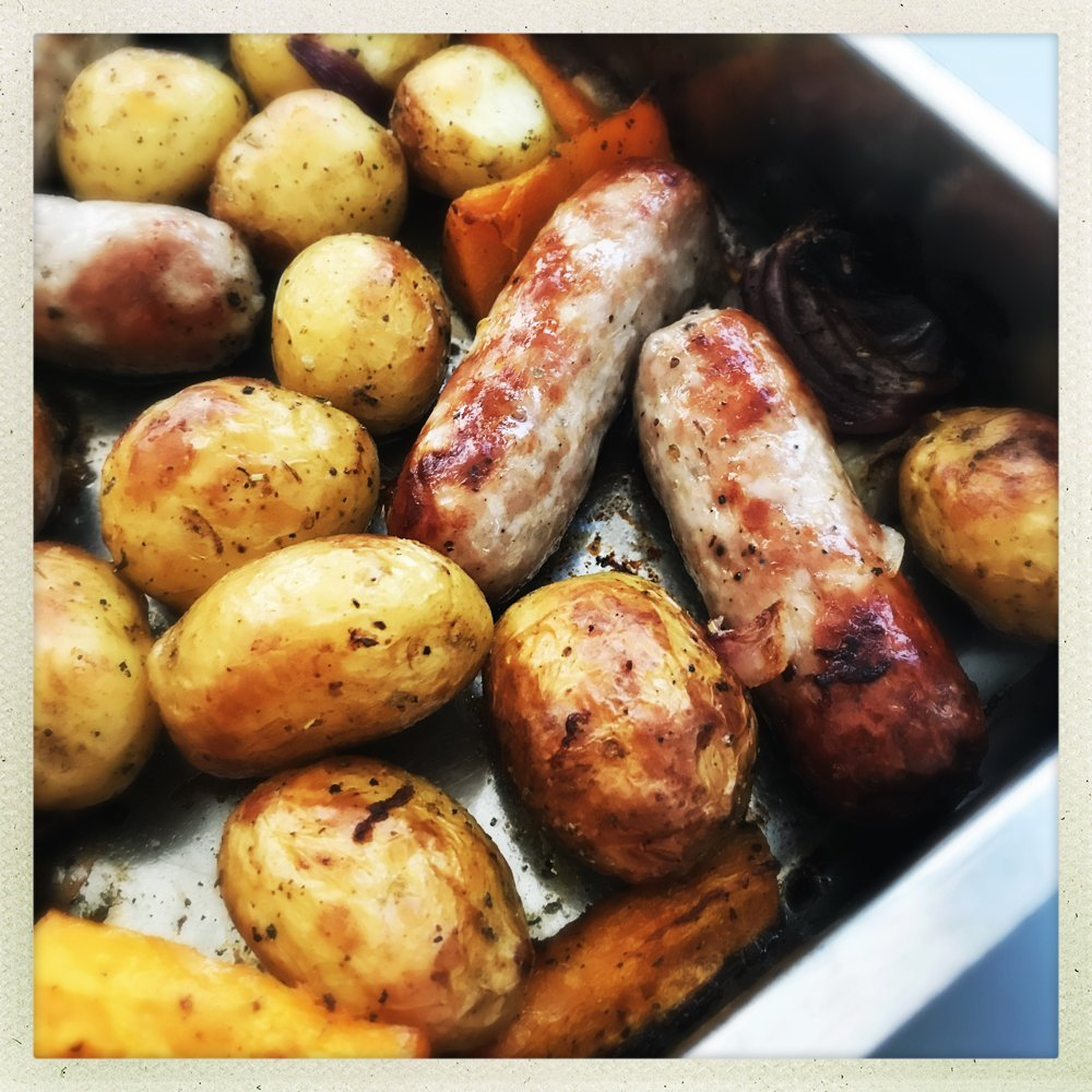 sausage traybake with butternut squash, potatoes and onions in a large roasting tin