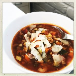 bowl of homemade minestrone soup with cheese shavings