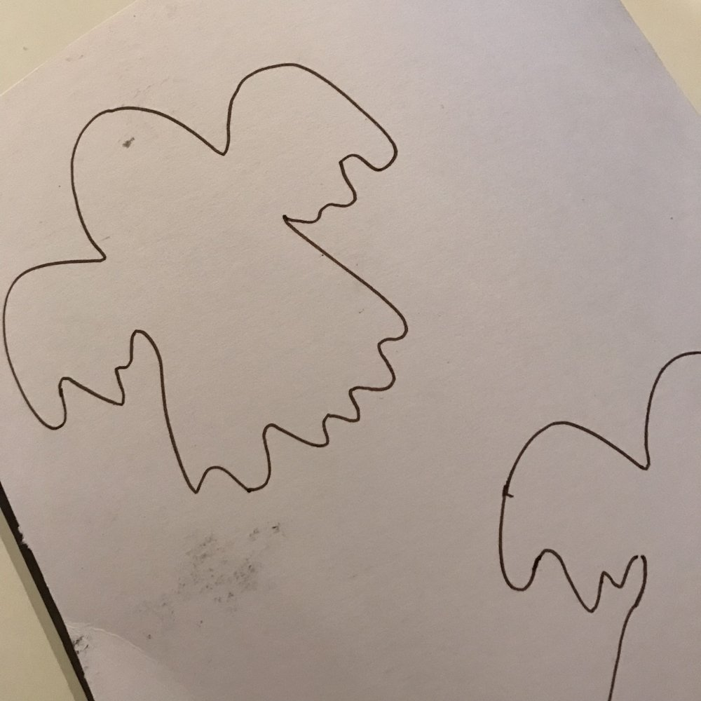 making Halloween tree decorations - ghosts cut out of cardboard