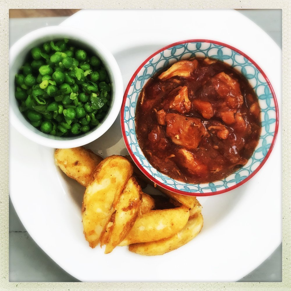 slow cooker peri peri chicken casserole served with pile of oven backed wedges and homemade Nando's style peas