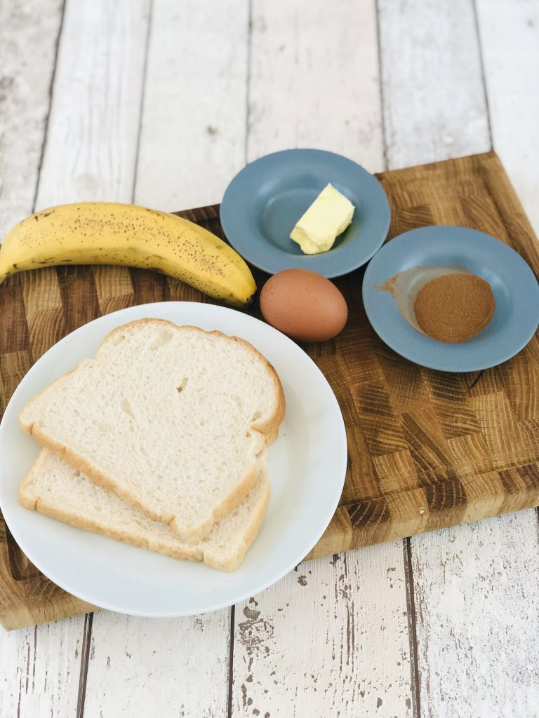 banana cinnamon french toast ingredients on a wooden chopping board - white sliced bread, banana, egg, butter and a little saucer with cinnamon on it