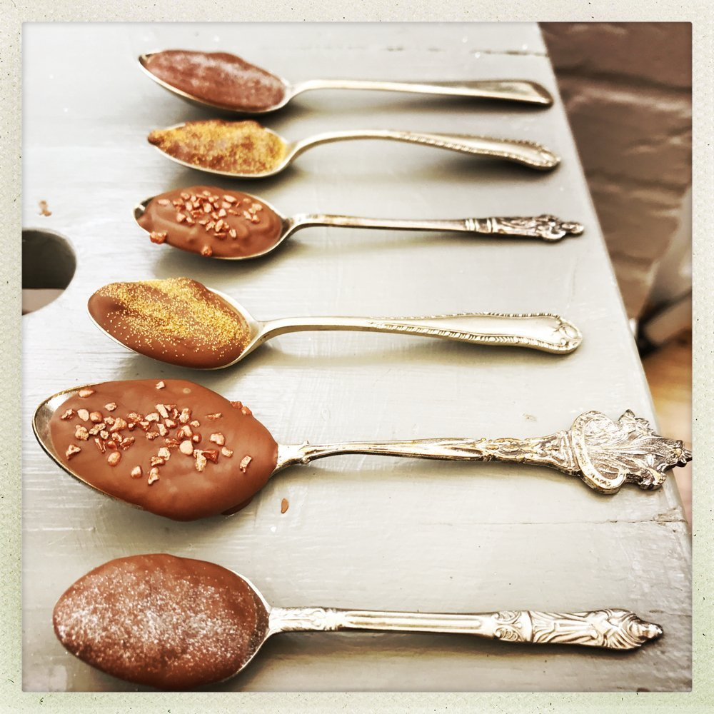 homemade vintage chocolate dipping spoons sprinkled with edible glitter on a rustic grey table