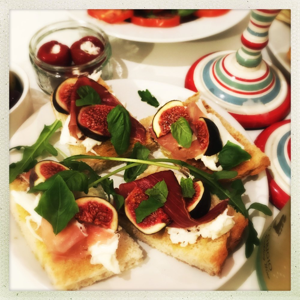 platter of fig and parma ham bruschetta topped with torn basil leaves. Small bowl of pepprdew stuffed peppers in the background