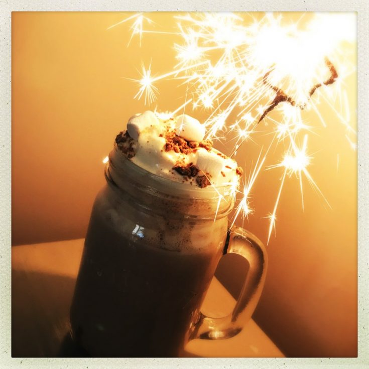 salted caramel hot chocolate with cream, marshmallows and a sparkler