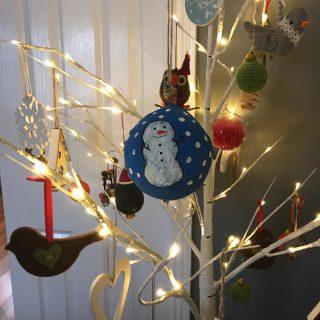 paper mâché snowman bauble hung in a Scandinavian style Christmas tree