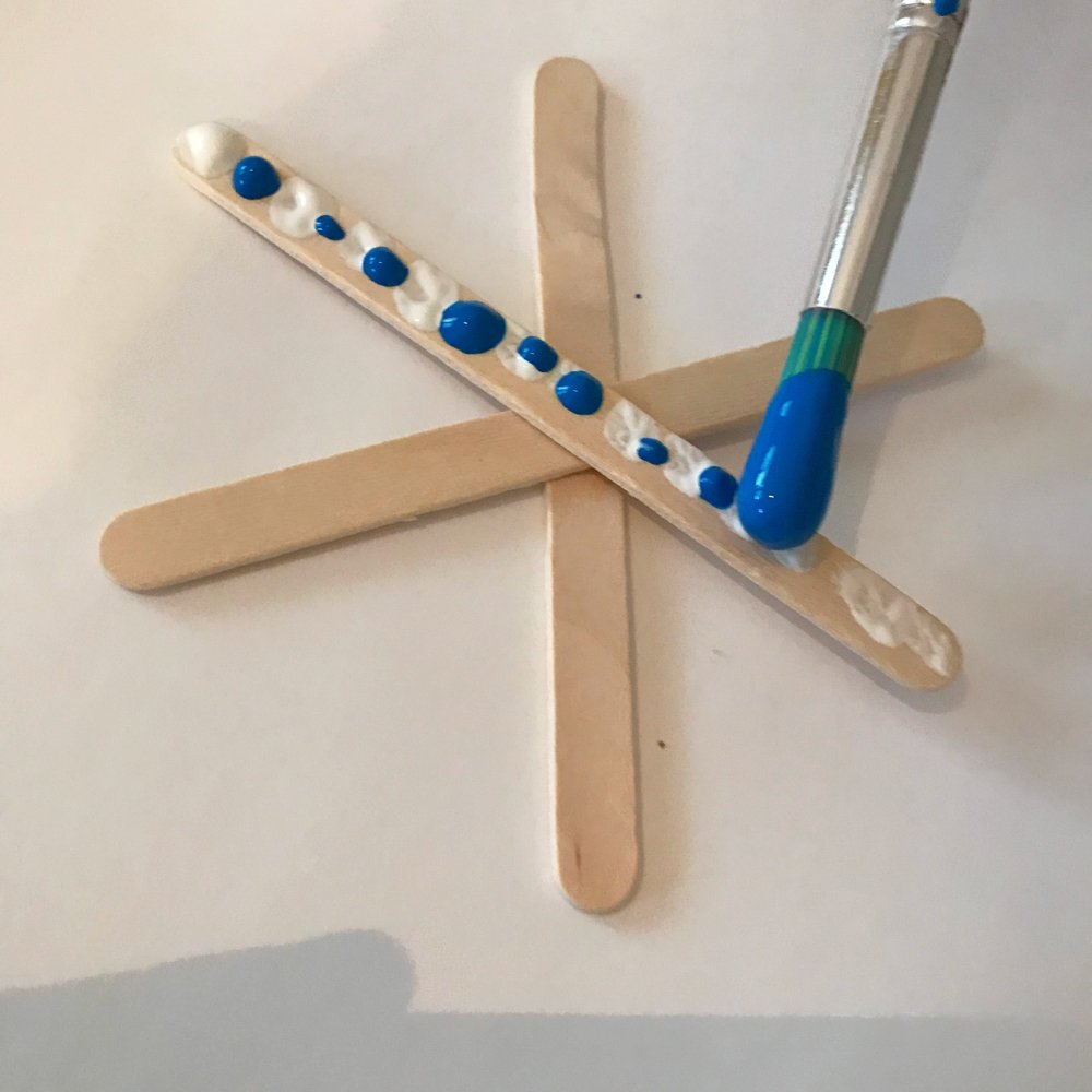 painted lollipop sticks stuck together to make snowflake ornament