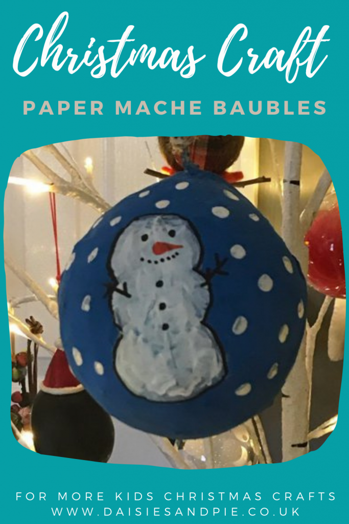 """homemade paper mache Christmas bauble decorated with snowman design and hung from a Scandinavian white twig Christmas tree Text overlay """"Christmas crafts - paper mache bauble - more kids Christmas crafts www.daisiesandpie.co.uk"""""""