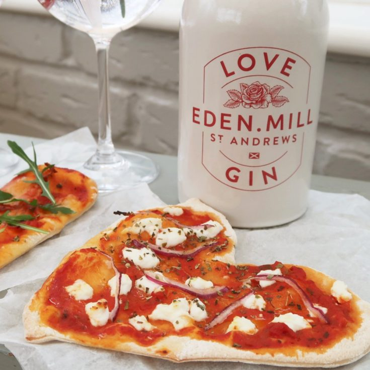 Bottle of Eden Mills gin next to a homemade heart shaped pizza topped with goats cheese and red onions