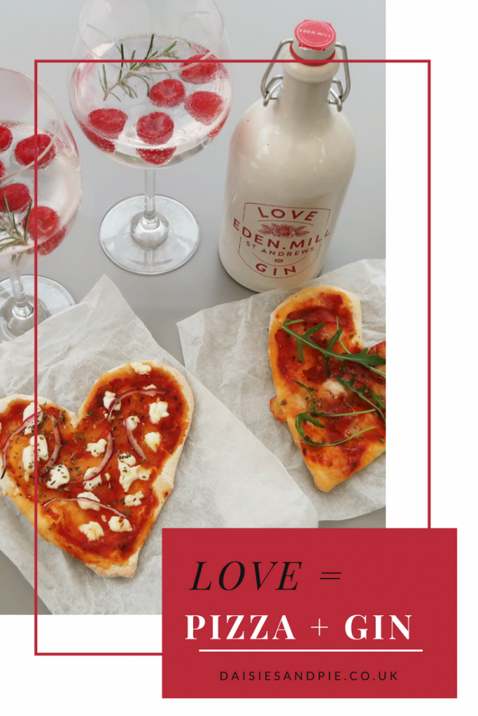 "Heart shaped homemade pizza topped with goats cheese and red onions, alongside Eden Mills gin and two gin cocktails garnished with raspberries and fresh rosemary. Text overlay saying ""Love = Gin + Pizza"""